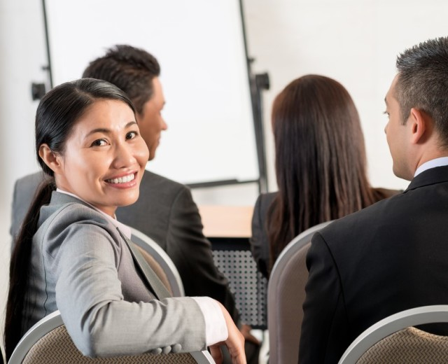 shutterstock_woman at meeting turning in chair (2)