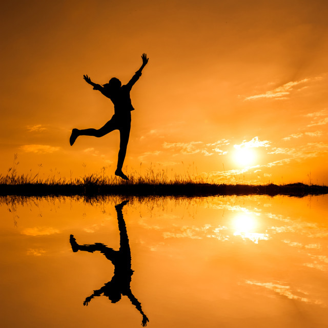 shutterstock_woman jumping reflection sunrise